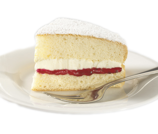 adm sponge cake slice with buttercream and jam on a plate with a fork